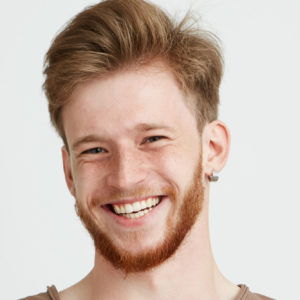 Portrait of happy cheerful young man with beard smiling looking at camera with crossed arms over white background. Copy space.
