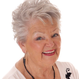A lovely senior woman in her seventies in a portrait image smiling looking in camera, isolated for white background.